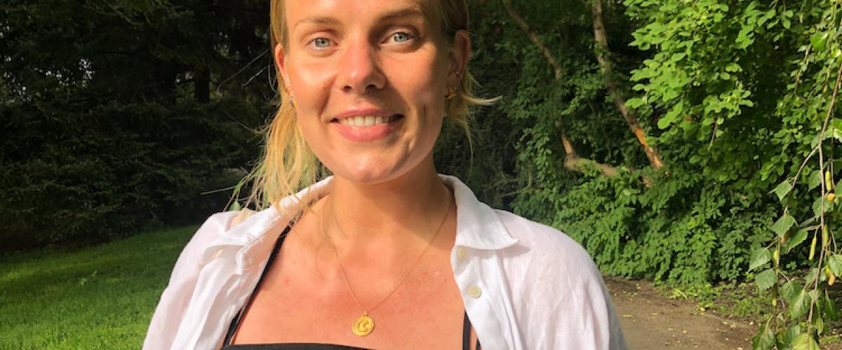 Utsnitt av større bilde: Hannah smiler mot kameraet, ikledd svart kjole og hvit skjorte, med grønne trær i bakgrunnen.